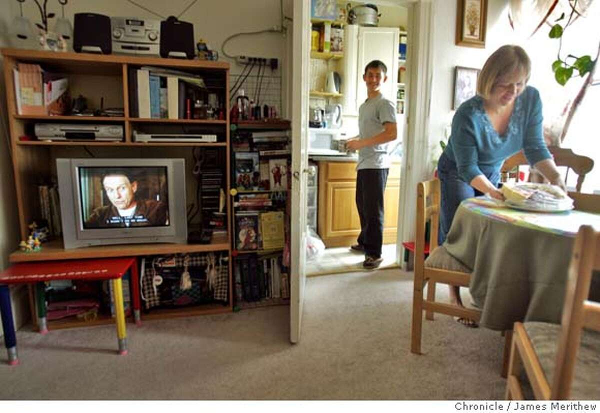 Andrey Pfening,17, helps his mother, Viktoriya, set the table at his family home on Clement Street in San Francisco, CA. July 07, 2007. Jim Merithew/The Chronicle