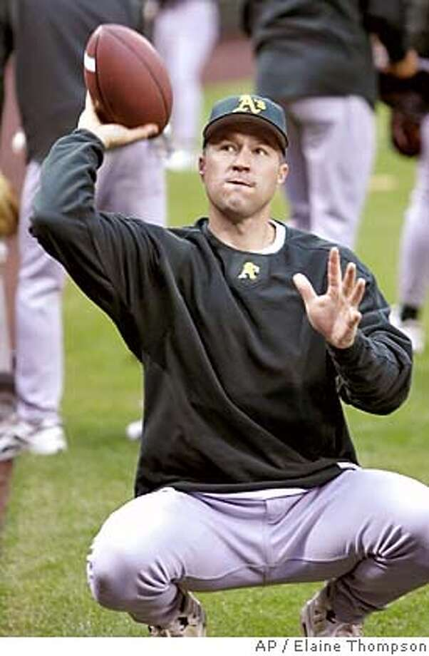 Oakland Athletics' Adam Melhuse throws a football before warm-ups before the team's baseball game against the Seattle Mariners, Friday, Sept. 30, 2005, in Seattle. The Athletics are out of playoff contention this season. (AP Photo/Elaine Thompson) Ran on: 10-01-2005 Ran on: 10-01-2005 Photo: ELAINE THOMPSON