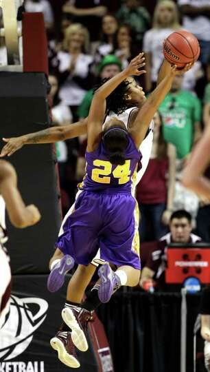 Albany's Adrienne Jones (24) has her shot blocked by Texas A&M's Tyra White during the first hal