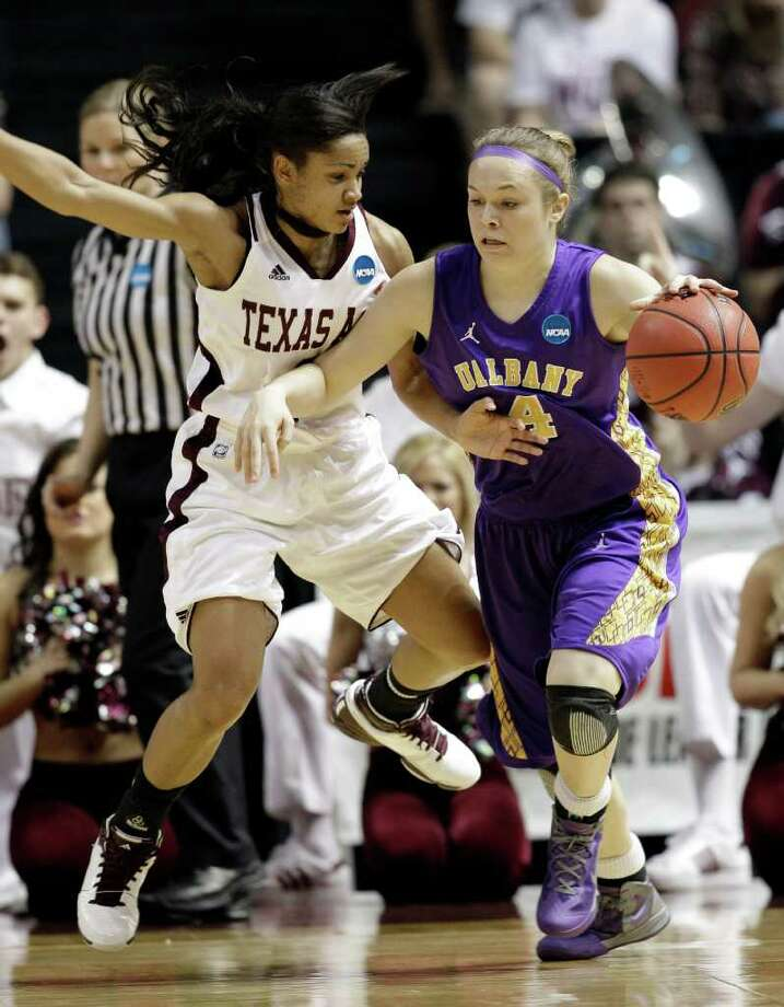 Albany's Sarah Royals (4) tries to drive around Texas A&M's Sydney Carter, left, during the first half of an NCAA tournament first-round college basketball game onSaturday, March 17, 2012, in College Station, Texas. (AP Photo/David J. Phillip) Photo: David J. Phillip