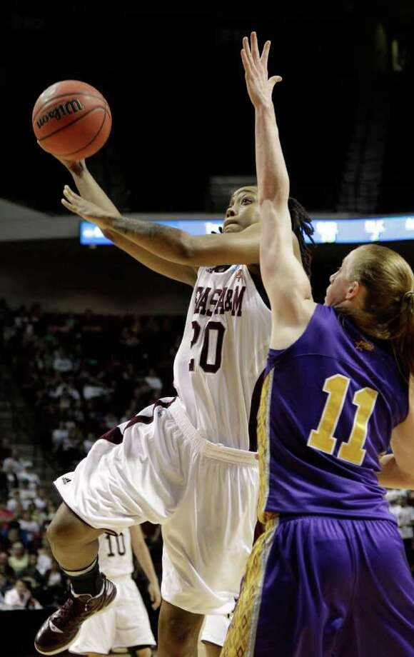 Texas A&M's Tyra White (20) goes up for a shot as Albany's Julie Forster (11) defends during the first half of an NCAA tournament first-round college basketball game on Saturday, March 17, 2012, in College Station, Texas. (AP Photo/David J. Phillip) Photo: David J. Phillip