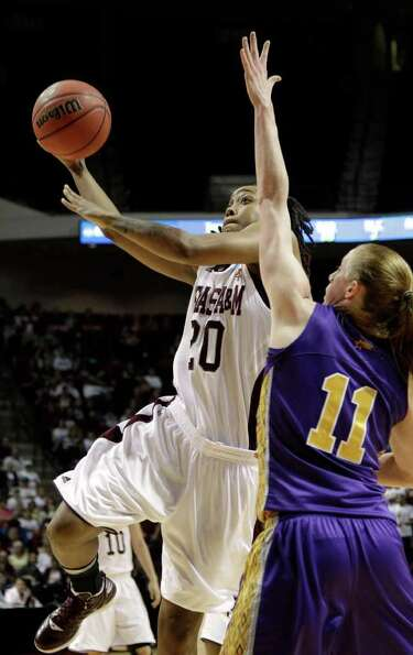 Texas A&M's Tyra White (20) goes up for a shot as Albany's Julie Forster (11) defends during the