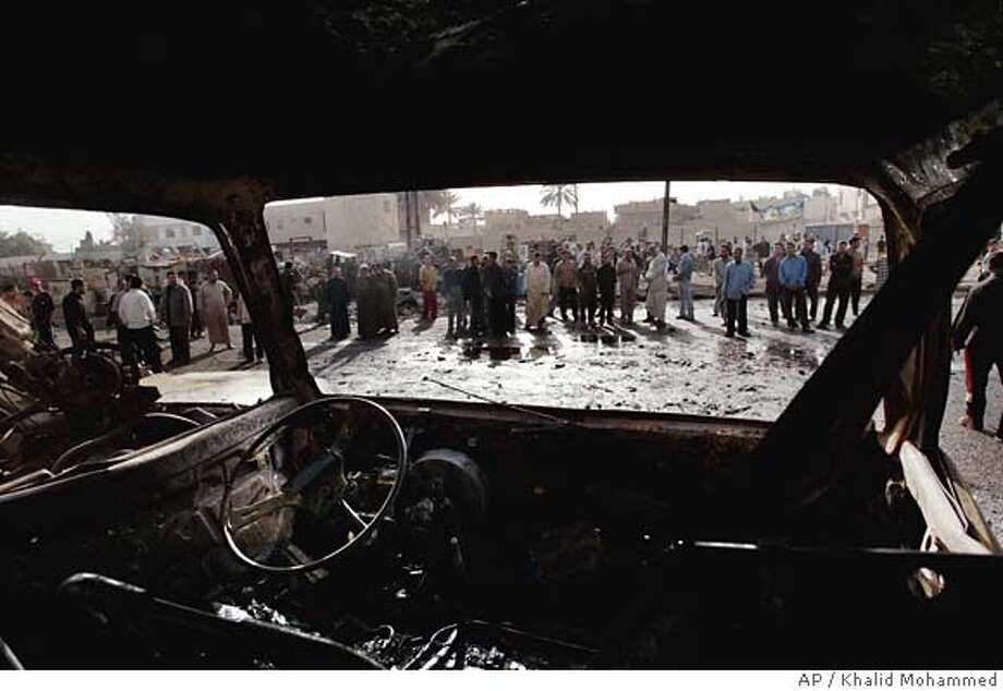 Iraqis view burnt out cars at the site of the bomb explosions in Shiite district of Sadr City, in Baghdad, Iraq, Monday, March 13, 2006. The feared resumption of mass sectarian violence erupted in a Baghdad Shiite slum when bombers blew apart two markets shortly before sundown, killing at least 44 people and wounding about 200 on Sunday. The bloody assaults on Sadr City came only minutes after Iraqi political leaders said the new parliament will convene Thursday. (AP Photo/Khalid Mohammed) Photo: KHALID MOHAMMED