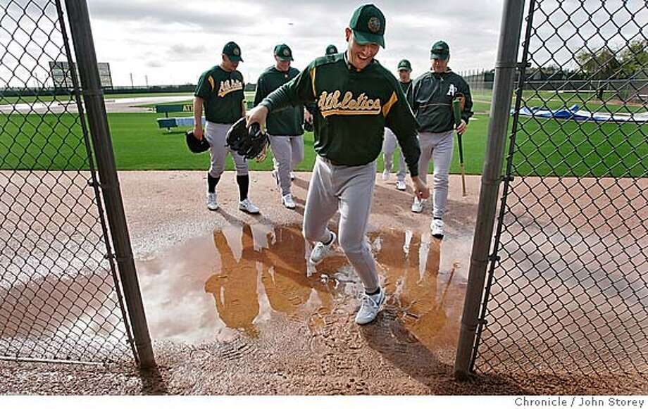 022005_Athletics_jrs701.JPG  A's Pitcher Justin Duchscherer jumps over a puddle in one the dugouts during the first day of spring training.  The Oakland A's first day of Spring Training in Phoenix. Event on 2/20/05 in Phoenix. John Storey / The Chronicle  contest yip MANDATORY CREDIT FOR PHOTOG AND SF CHRONICLE/ -MAGS OUT Photo: John Storey