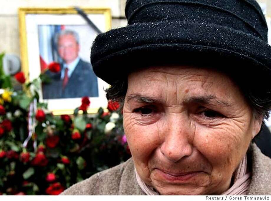 A woman cries in front of a picture of former Yugoslav president Slobodan Milosevic in front of the Serbian Social Party headquarters in Belgrade March 13, 2006. Dutch public prosecutors said on Monday they had released the body of Milosevic, who died at the detention centre of the U.N. war crimes tribunal in The Hague on Saturday. REUTERS/Goran Tomasevic 0 Photo: GORAN TOMASEVIC