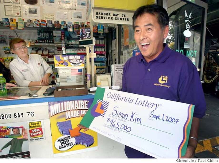 Simon Kim, owner of the Harbor Bay 76 gas station, smiles while holding the ceremonial check he received for selling the winning lottery ticket in Alameda, Calif. on Thursday, Sept. 6, 2007. His brother Danny (background) actually sold the winning $93 million lottery ticket to a customer at the station on August 31 but who has yet to come forward to claim the prize.  PAUL CHINN/The Chronicle  **Simon Kim, Danny Kim Photo: PAUL CHINN
