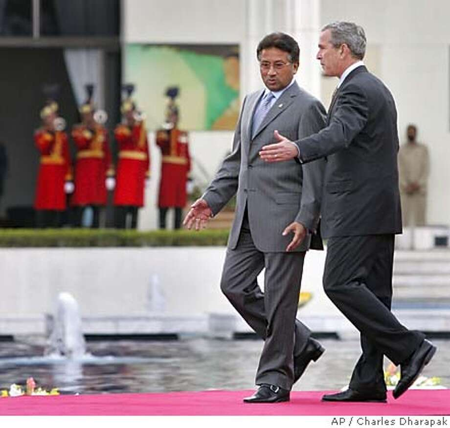 """U.S. President George W. Bush, right, and Pakistani President Pervez Musharraf walk together to a joint press availability at Aiwan-e-Sadr, or """"house of the President"""", in Islamabad, Pakistan, Saturday, March 4, 2006. President Bush showed solidarity Saturday with Pakistani President Gen. Perez Musharraf's war-on-terror alliance with the United States, a stance that is at odds with many in this Islamic nation. (AP Photo/Charles Dharapak)Ran on: 03-05-2006  President Bush and Pakistani President Pervez Musharraf walk to a joint news conference at the presidential palace in Islamabad.Ran on: 03-05-2006  President Bush and Pakistani President Pervez Musharraf walk to a joint news conference at the presidential palace in Islamabad. Photo: CHARLES DHARAPAK"""