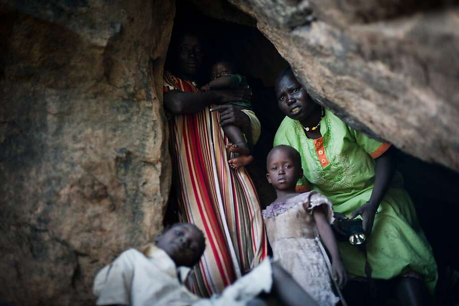 TO GO WITH AFP STORY BY IAN TIMBERLAKE (FILES)  - A picture dated July 1, 2011 shows a terrified mother looking out of a cave as she takes shelter from an aircraft flying over the hills surrounding Lwere in Sudan's Nuba mountains on as hundreds of families have fled their villages in South Kordofan following recent bombing by the Sudanese armed forces. A hidden war affecting hundreds of thousands of people as tensions mount between Sudan and the newly independent South Sudan threatens to erupt into direct conflict, analysts and diplomats say. AFP PHOTO/PHIL MOORE (Photo credit should read PHIL MOORE/AFP/Getty Images) Photo: Phil Moore, AFP/Getty Images