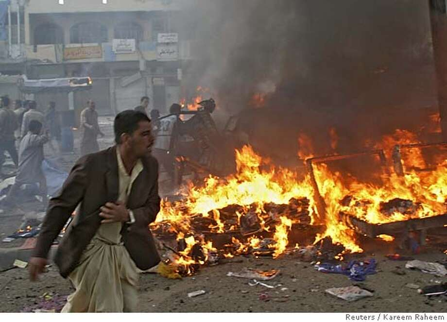 Man runs past burning debris at market after series of bomb attacks in Baghdad's Sad'r city Photo: KAREEM RAHEEM