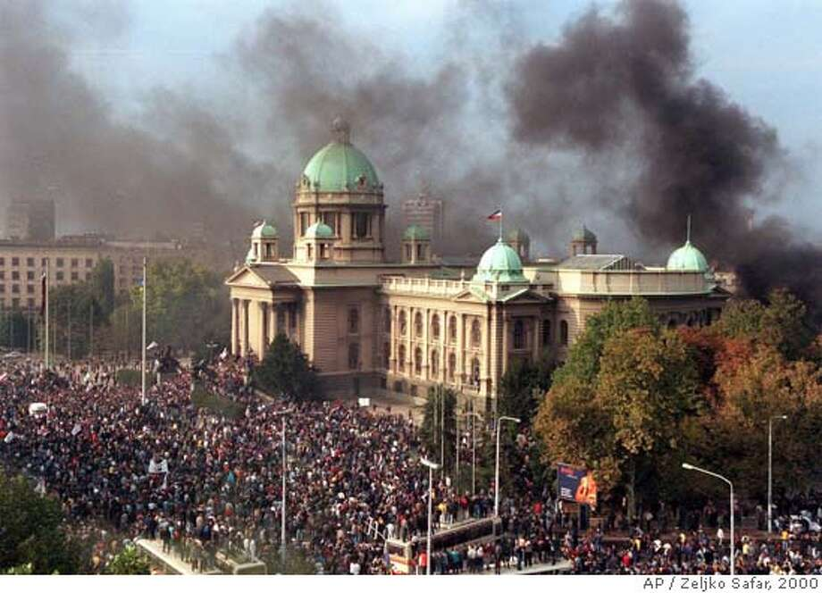 ** FILE ** Smoke rises from the Yugoslav federal parliament in Belgrade in this Oct. 5, 2000 file picture. Angry crowds gathered in front of the parliament while columns of protesters streamed into the capital for a mass rally intended as the final push against embattled president Slobodan Milosevic. Milosevic, the former Yugoslav and Serbian president who orchestrated the Balkan wars of the 1990s and was on trial for war crimes, was found dead in his prison cell at the U.N. detention center near The Hague, the U.N. tribunal said Saturday March 11, 2006. (AP Photo/Zeljko Safar) ** YUGOSLAVIA OUT ** COMMERCIAL ONLINE OUT ** YUGOSLAVIA OUT COMMERCIAL ONLINE OUT OCT. 5, 2000 FILE PICTURE Photo: ZELJKO SAFAR
