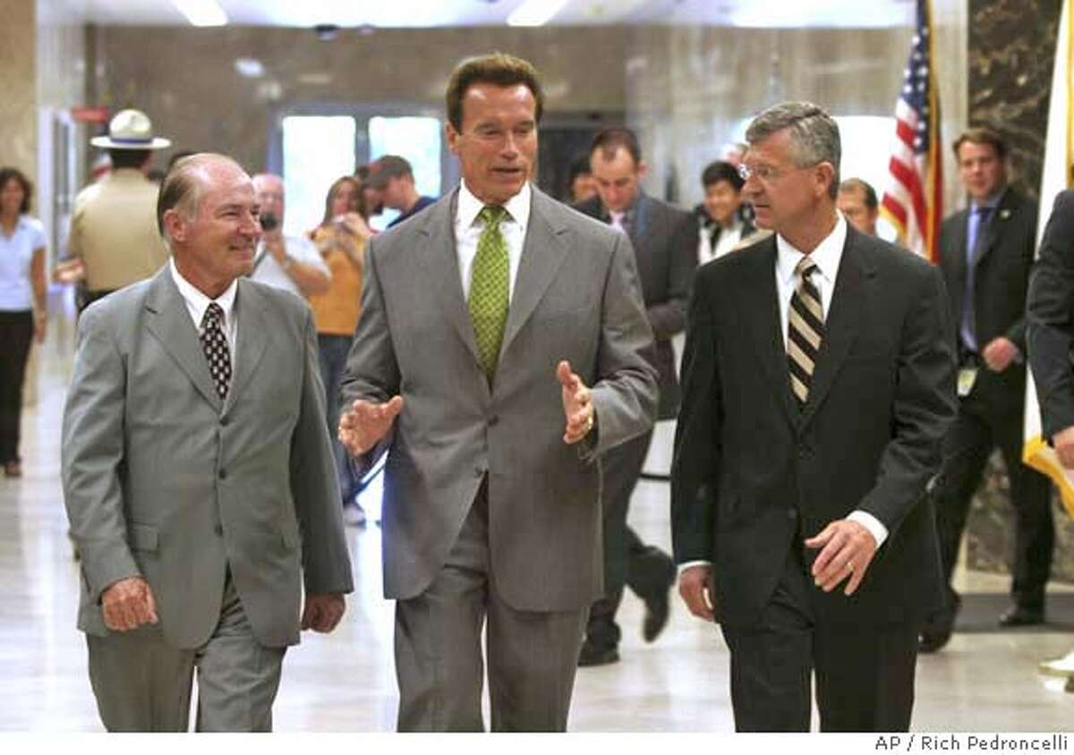 ** CORRECTS NAME TOEBBEN ** Gov. Arnold Scharzenegger, center, talks with Los Angeles Chamber of Commerce President and CEO Gary Toebben, right, and chairman of the board David Fleming, left, as they walk to a Capitol news conference Sacramento, Calif., Monday, Sept. 17, 2007. The pair announced the chamber's endorsement of Schwarzeneggers health care reform plan. While answering questions Schwarzenegger said he would veto a gay marriage bill approved by the legislature in the closing days of the legislative session. (AP Photo/Rich Pedroncelli) CORRECTS NAME TOEBBEN