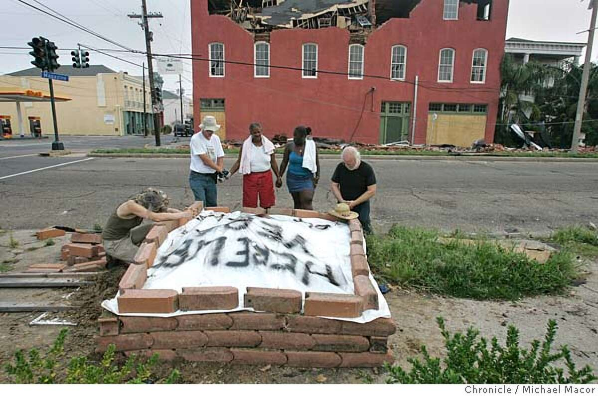 katrina3_160_mac.jpg l to r- Maggie McEleney, John Lee, Janet Clouden, Kema Smith and Patrick McCarthy, join in prayer for their neighbor and friend, Vera Smith, they just buried on a street corner near their homes. Their friend had been killed by a hit and run driver last Tuesday and left at the corner of Jackson and Magazine Sts. in the Lower Garden District, north of downtown New Orleans. After friends and neighbors alerted police and other officials passing by the scene, their request to remove the body was never answered. This morning the group took the matter into their own hands and buried their friend themselves.The aftermath of Hurricane Katrina that ravaged the gulf coast states, with New Orleans, Louisiana taking the brunt of the killer storm. 9/3/05 New Orleans , La Michael Macor / San Francisco Chronicle Mandatory Credit for Photographer and San Francisco Chronicle/ - Magazine Out