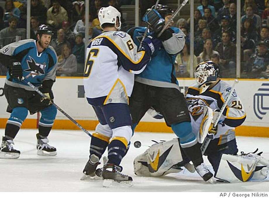 San Jose Sharks' Milan Michalek, left, shoots, but has his shot blocked by Nashville Predators goalie Tomas Vokoun, right, as Predators' Shea Weber, (6) struggles with Sharks' Scott Thornton, in the second period of an NHL hockey game, Saturday, March 11, 2006, in San Jose, Calif. (AP Photo/George Nikitin) Photo: GEORGE NIKITIN