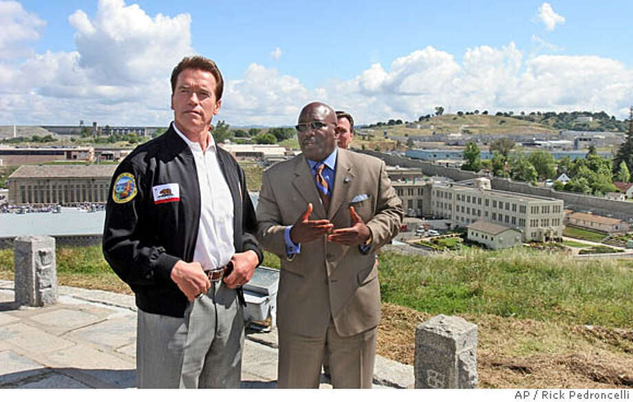 Gov. Arnold Schwarzenegger (left) and Roderick Hickman, secretary of the Youth and Adult Correctional Agency, stand on a hillside above Folsom State Prison. Associated Press file photo, 2005, by Rich Pedroncelli