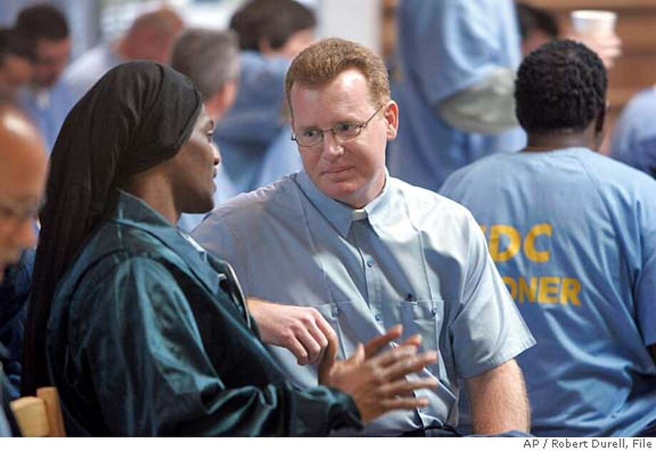 The Rev. James Tramel , center, facing camera, speaks to a fellow inmate during a service to celebrate the Feast of the Epiphany at Solano State Prison in Vacaville, Calif., Jan. 12, 2006. Tramel preaches four times a year to members of The Episcopal Church of the Good Shepherd in Berkeley, Calif. On Sunday, March 12, 2006, parishioners will finally get to meet him _ after he's released from prison. Tramel, 38, who was convicted of second-degree murder in 1986, has been reaching out to Berkeley churchgoers by telephone from Solano State Prison in Vacaville, where he was ordained last year. He will be paroled Sunday. (AP Photo/Los Angeles Times, Robert Durell) ** MANDATORY CREDIT ** NO MAGS NO TV NO FOREIGN ** ***MANDATORY CREDIT: PHOTOG NAME/LOS ANGELES TIMES*** MANDATORY CREDIT***, , NO FOREIGN, NO MAGS, NO TELEVISION*** LOS ANGELES DAILY NEWS OUT, ORANGE COUNTY REGISTER OUT, VENTURA COUNTY STAR OUT, INLAND VALLEY DAILY BULLETIN OUT, SAN BERNARDINO SU Photo: ROBERT DURELL