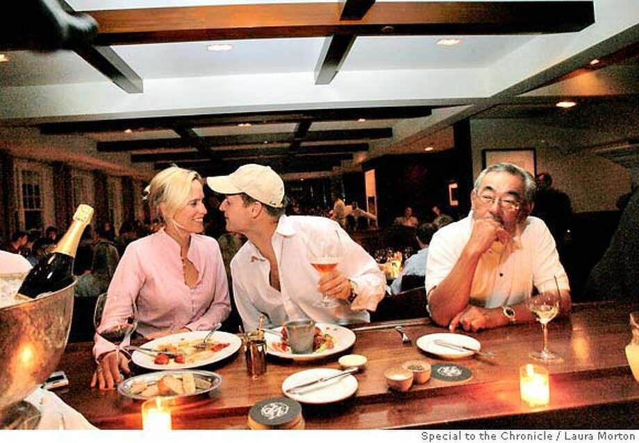 BARBITES20_0017_LKM.jpg Gina and Duff Baldwin (left) share a meal and some drinks while Thomas Oku (right) relaxes with a glass of wine at the bar in Village Pub in Woodside, CA. The popular meeting place has a bar area in addition to the restaurant. (Laura Morton/Special to the Chronicle) ** Gina Baldwin  *** Duff Baldwin  *** Thomas Oku Photo: Laura Morton