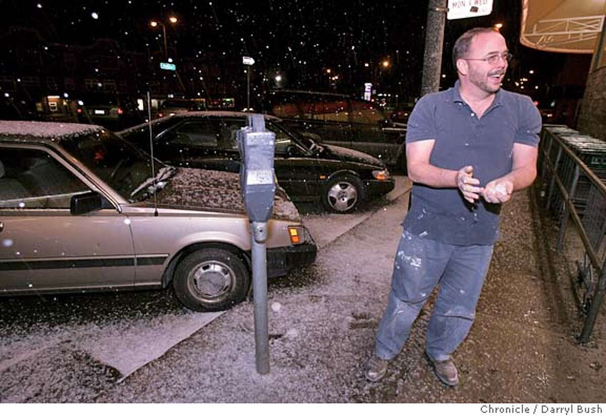 Paul Riley of San Francisco makes a snow ball on the sidewalk as a hail storm made for some snow-like for shoppers at a Mollie Stone market on Portola Ave. near Twin Peaks. Event on 3/10/06 in San Francisco. Darryl Bush / The Chronicle