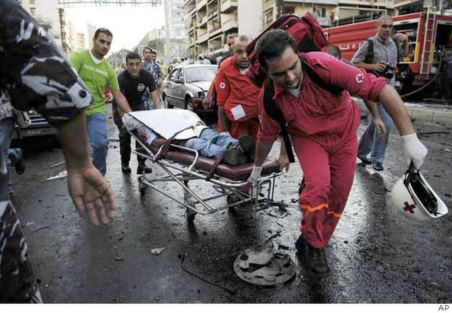 Red cross workers take away a body after an explosion in Beirut, Lebanon, Wednesday, Sept. 19, 2007. A powerful bomb killed a pro-government Parliament member and six others Wednesday in a Christian suburb east of the Lebanese capital, security officials said. The blast targeted Antoine Ghanem, 64, a member of the right-wing Christian Phalange Party, said the officials, speaking on condition of anonymity because they were not authorized to speak to the press. (AP Photo) Photo: STR