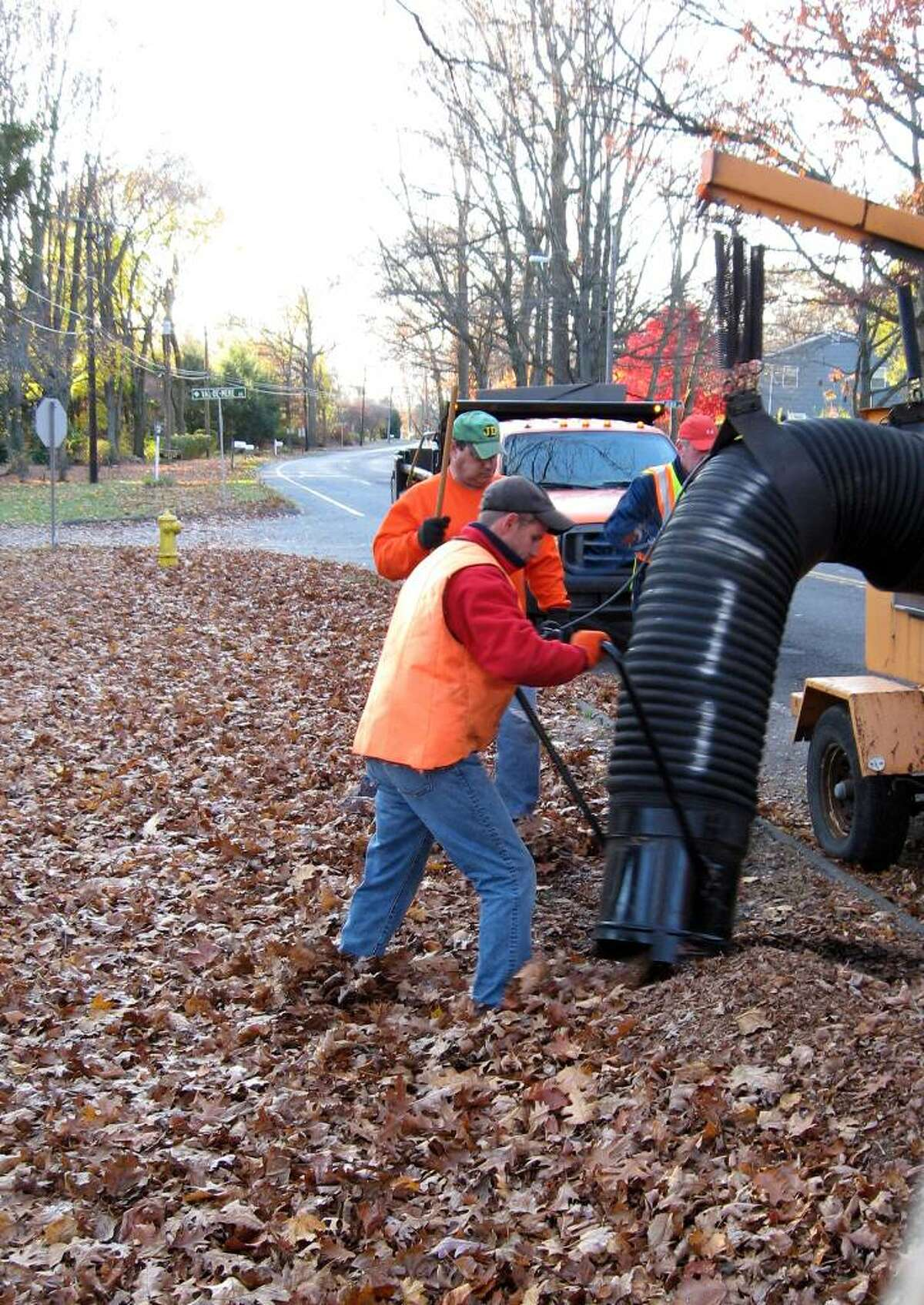 Rich Infante, left, and Jim McGuire of the Trumbull DPW operate a leaf vacuum, which is used on busier streets that can't be closed off. Elsewhere, Payloaders and dump trucks do the leaf-pickup job, but there's still a lot of raking involved.