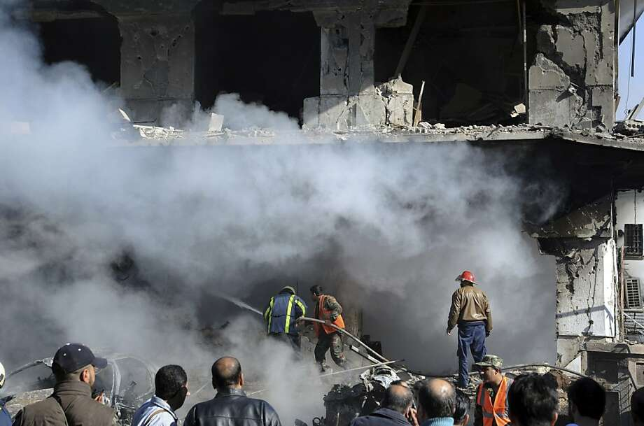 In this photo released by the Syrian official news agency SANA, Syrian firefighters extinguish a fire in a damaged building near the aviation intelligence department, which was attacked by one of two explosions, in Damascus, Syria, on Saturday, March 17, 2012. Twin bombings struck government targets in the Syrian capital early Saturday, killing security forces and civilians and leaving pools of blood and carnage in the streets, according to state-run television. Photo: Anonymous, Associated Press