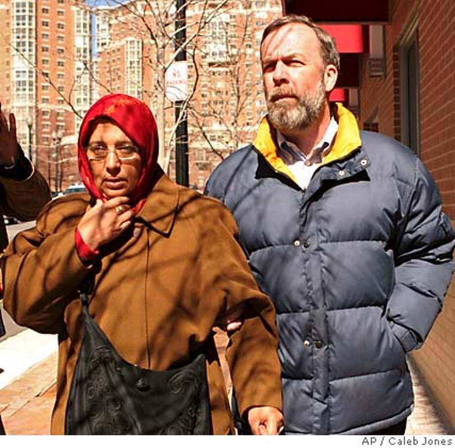 Aicha El-wafi, left, mother of confessed al-Qaida conspirator Zacarias Moussaoui, leaves U.S. District Court in Alexandria, Va. Tuesday, March 7, 2006 with an unidentified man after attending her son's trial. (AP Photo/Caleb Jones) Photo: CALEB JONES
