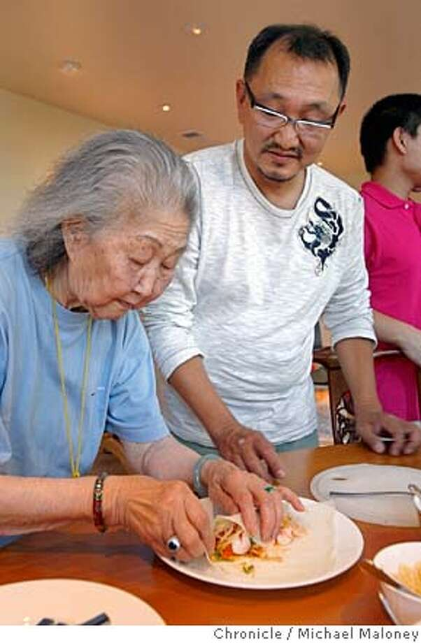 Chris Yeo watches as his mom Jenny Lim expertly prepares her popia.  The Chinese mid Autumn Moon festival starts Sept. 23 and chef/restaurateur Chris Yeo celebrates it by having his extended family gather for a large family meal and autumn moon cakes at his Hillsborough, CA home. Recipes includ popia, tea leaf salad, and the moon cakes. (NOTE : the food and this gathering of the Yeo's was at the Chronicle's request - the photos are set up)  Photo taken on 8/29/07 in Hillsborough, CA  Photo by Michael Maloney / San Francisco Chronicle  ***Chris Yeo, Jenny Lim MANDATORY CREDIT FOR PHOTOG AND SF CHRONICLE/NO SALES-MAGS OUT Photo: Michael Maloney