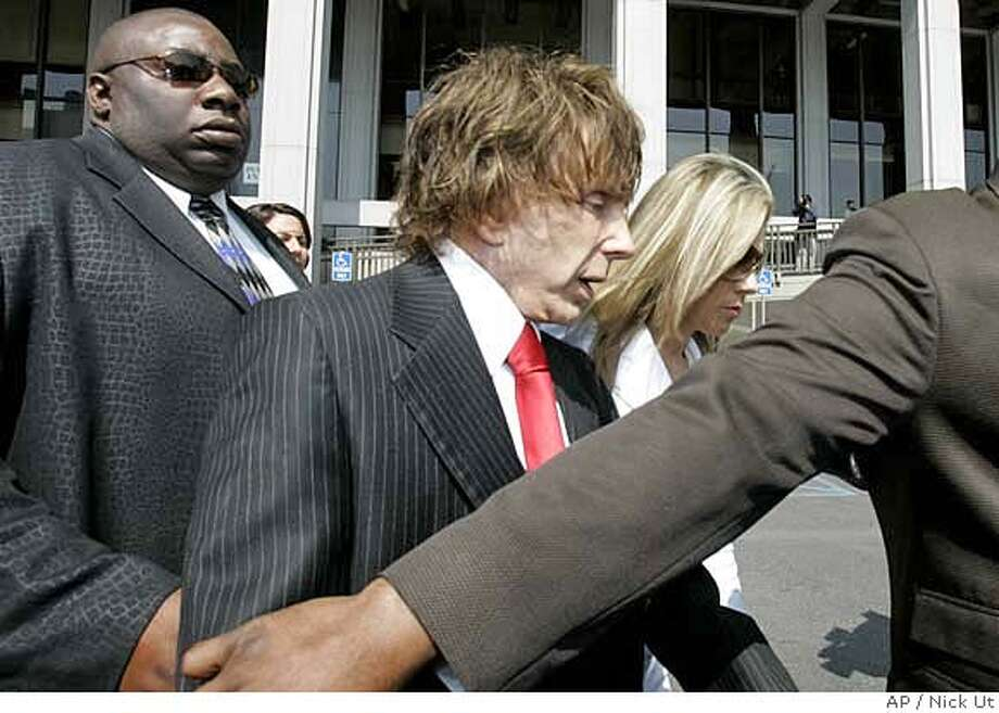 Phil Spector and his wife, Rachelle Spector, center, are escorted from court by bodyguards Tuesday, Sept. 18, 2007 in Los Angeles. The foreman of the jury in Phil Spector's murder trial said Tuesday that the panel is at an impasse, and the judge told lawyers he was considering allowing the panel to consider a lesser charge. (AP Photo/Nick Ut) Photo: Nick Ut