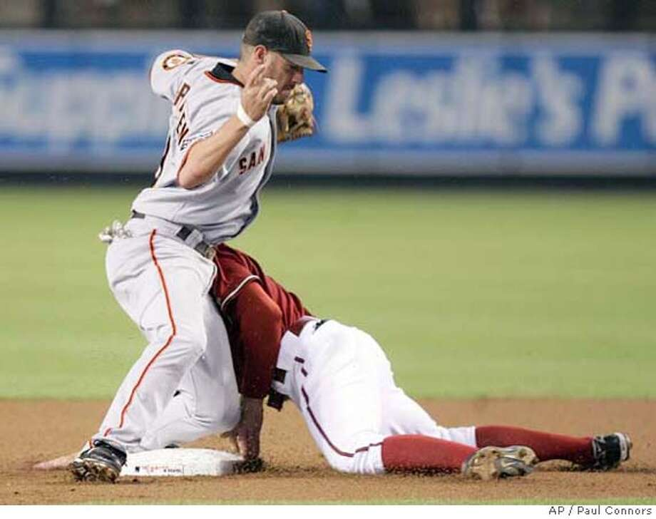 San Francisco Giants second baseman Kevin Frandsen, left, is run into by Arizona Diamondbacks' Eric Byrnes, right, after Byrnes was picked off during a steal attempt in the first inning of a baseball game Tuesday, Sept. 18, 2007, in Phoenix. (AP Photo/Paul Connors) Photo: Paul Connors