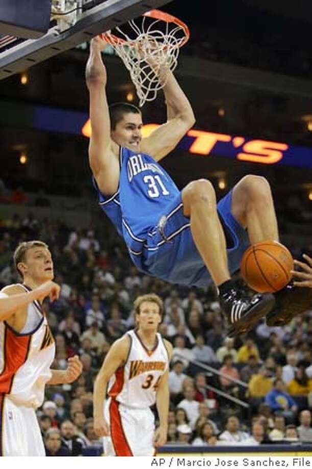 Orlando Magic's Darko Milicic (31), of Serbia-Montenegro, dunks as Golden State Warriors' Andris Biedrins, of Latvia, left, and Mike Dunleavy (34) watch during the second half of an NBA basketball game Wednesday, March 1, 2006, in Oakland, Calif. Golden State won 98-94. (AP Photo/Marcio Jose Sanchez) EFE OUT Photo: MARCIO JOSE SANCHEZ
