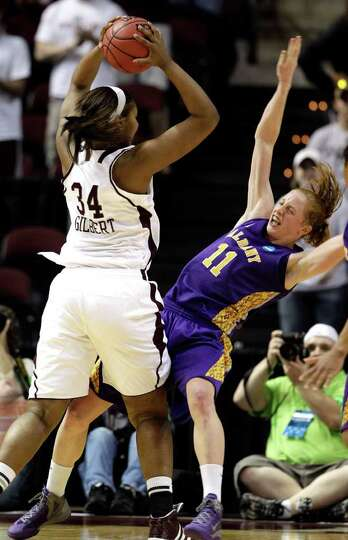 Texas A&M's Karla Gilbert (34) charges into Albany's Julie Forster (11) during the second half o