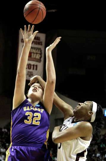 Albany's Megan Craig (32) is fouled by Texas A&M's Kelsey Bone (3) during the second half of an
