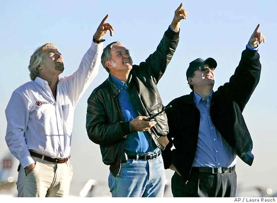 Richard Branson, left, Burt Rutan and Paul Allen watch as SpaceShipOne glides back to earth as the Mojave Aerospace Ventures Team wins the Ansari X Prize in Mojave, Calif. on Monday, Oct. 4, 2004. The $10 million prize goes to the first team to launch the weight equivalent of three people into suborbital space twice within a two week period. (AP Photo/Laura Rauch)