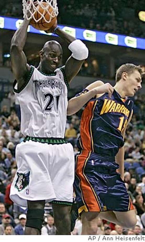 Minnesota Timberwolves forward Kevin Garnett (21) pulls down a rebound over Golden State Warriors center Andris Biedrins, right, of Latvia, during the first quarter of an NBA basketball game in Minneapolis, Sunday, March 5, 2006. Garnett scored 23 points and tied his season-high with 21 rebounds as the Timberwolves beat the Warriors, 103-90. (AP Photo/Ann Heisenfelt) Photo: ANN HEISENFELT