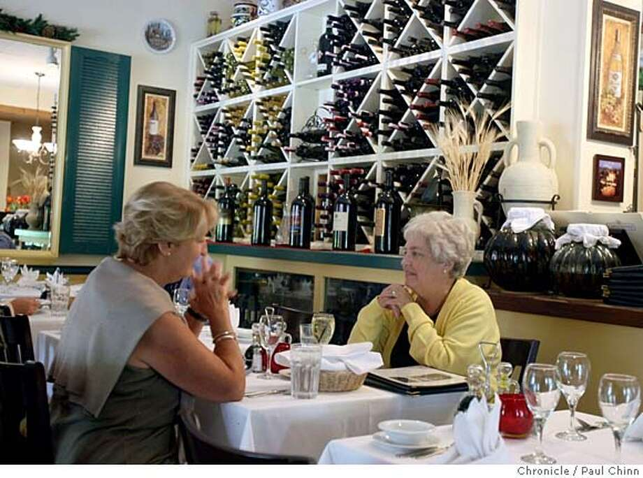 Two women enjoy lunch in front of a wall filled with wine at La Finestra Italian restaurant in Lafayette, Calif. on Wednesday, Sept. 12, 2007.  PAUL CHINN/The Chronicle MANDATORY CREDIT FOR PHOTOGRAPHER AND S.F. CHRONICLE/NO SALES - MAGS OUT Photo: PAUL CHINN