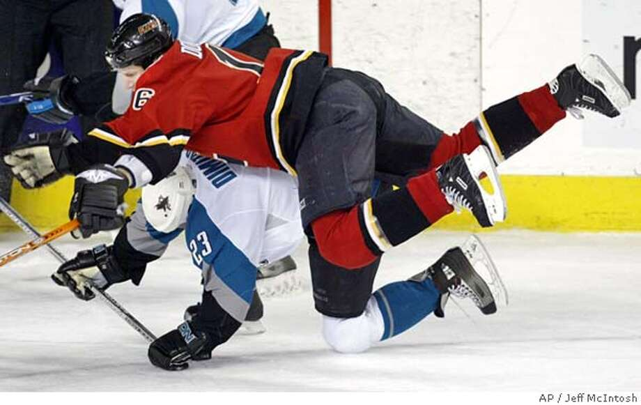 San Jose Sharks' Niko Dimitrakos, bottom, gets hammerd by Calgary Flames' Shean Donovan during first period NHL hockey action in Calgary, Canada, Saturday, March 4, 2006. Donovan received a tripping penalty on the play.(AP Photo/Jeff McIntosh,CP) Photo: JEFF MCINTOSH