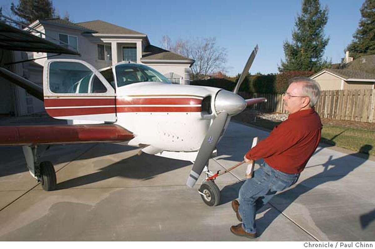 Burl Skaggs pulls a 1958 Bonanza J-35 out of the hangar before commuting to his job in Palo Alto from his home at Cameron Park Airpark Estates residential community in Cameron Park, Calif. on 2/24/06 where the streets are taxiways, planes park in driveways and nearly every home comes with a hangar. Skaggs makes the short flight to Palo Alto airport in 40 minutes. PAUL CHINN/The Chronicle MANDATORY CREDIT FOR PHOTOG AND S.F. CHRONICLE/ - MAGS OUT