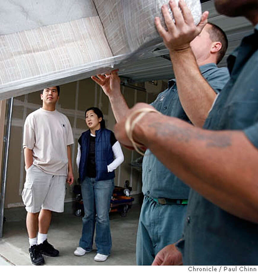 Mark and Wendy Kano (at left) watched movers unload their furniture when they finally moved into their new home in Hayward, Calif. on 2/18/06. The Chronicle has been following the construction of their new home in the Eden Shores development for the past year.  PAUL CHINN/The Chronicle MANDATORY CREDIT FOR PHOTOG AND S.F. CHRONICLE/ - MAGS OUT Photo: PAUL CHINN