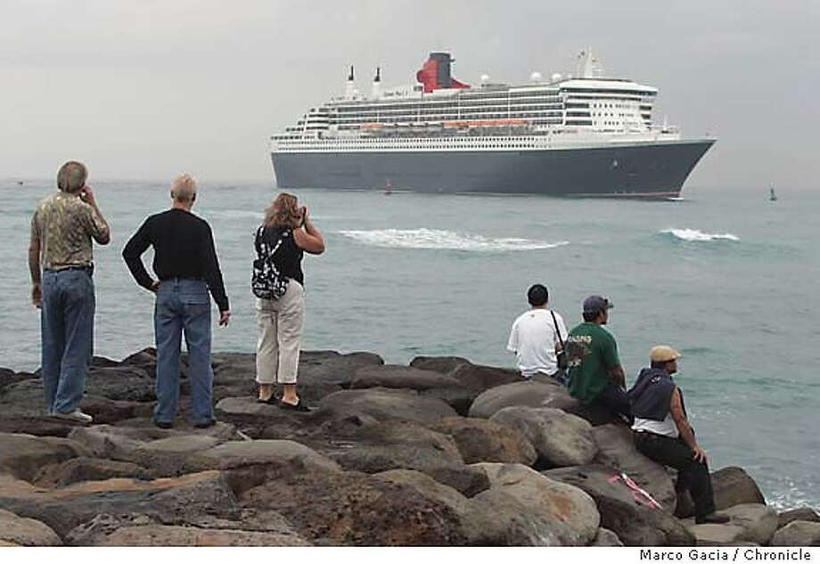 The mammoth Queen Mary 2 enters Honolulu Harbor as spectators watch on Wednesday. Associated Press photo by Marco Garcia