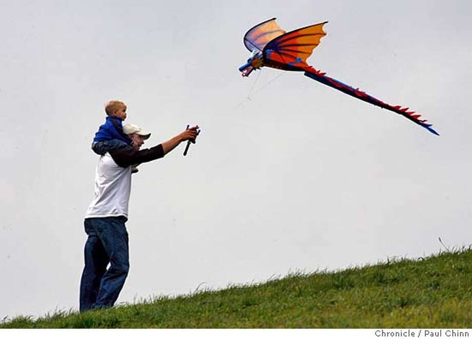 Nick Harris, of Walnut Creek, and his 21-month-old son Drew take advantage of a break between storms to fly a dragon kite at Cesar Chavez Park in Berkeley, Calif. on 3/4/06. A new round of storms are expected to drench the Bay Area for the next several days.  PAUL CHINN/The Chronicle MANDATORY CREDIT FOR PHOTOG AND S.F. CHRONICLE/ - MAGS OUT Photo: PAUL CHINN