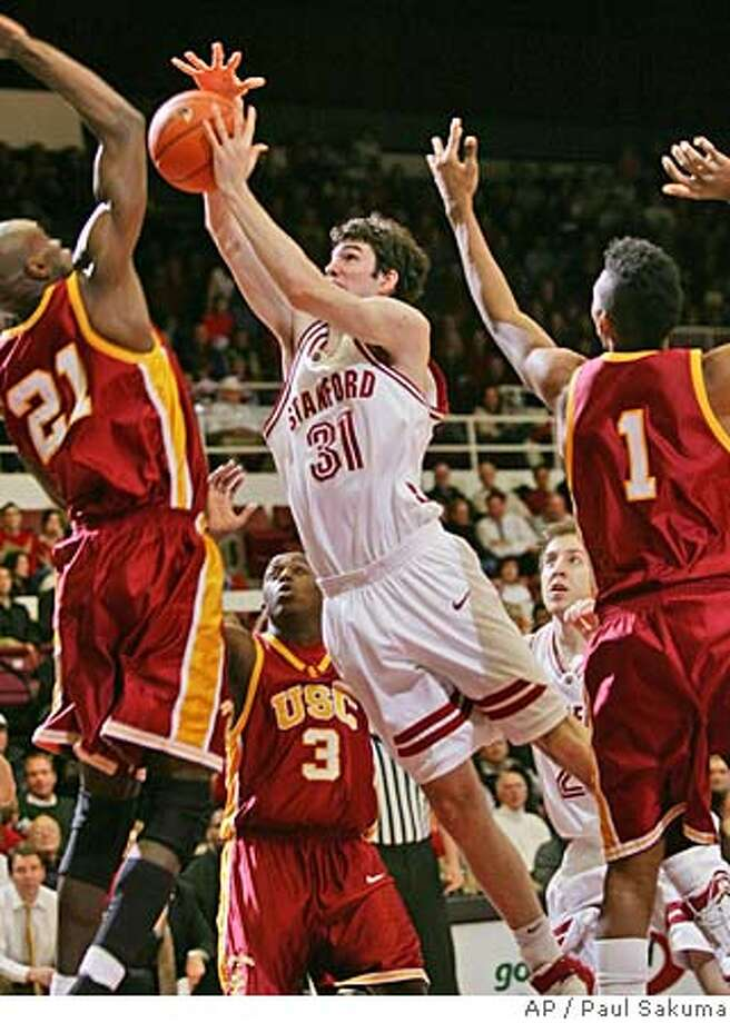 Stanford forward Taj Finger (31) drives to the basket in front of Southern California center Abdoulaye Ndiaye (21) and forward Nick Young (1) during the first half of a college basketball game Thursday, March 2, 2006, in Stanford, Calif. (AP Photo/Paul Sakuma) Photo: PAUL SAKUMA