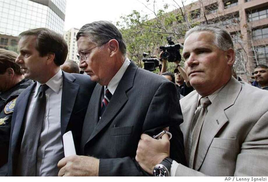 "Former U.S. Congressman Randall ""Duke"" Cunningham, center, is helped by aides as he arrives at the federal courthouse in San Diego Friday March 3, 2006 for sentencing on his conviction for bribery and tax evasion. (AP Photo/Lenny Ignelzi) Photo: LENNY IGNELZI"