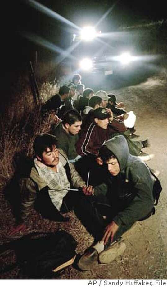 "** FILE ** Detained, suspected illegal immigrants, illuminated by U.S. Border Patrol vehicle lights, await transport in the Otay Mesa Mountain Range, near Dulzura, Calif., Oct. 12, 2005. The Senate on Thursday March 2, 2006, took up what a key senator called the ""gigantic task"" of tightening U.S. borders against illegal immigration, while maintaining the flow of low-wage workers for U.S. business. (AP Photo/Sandy Huffaker, File) OCT 12 2005 FILE Photo: SANDY HUFFAKER"