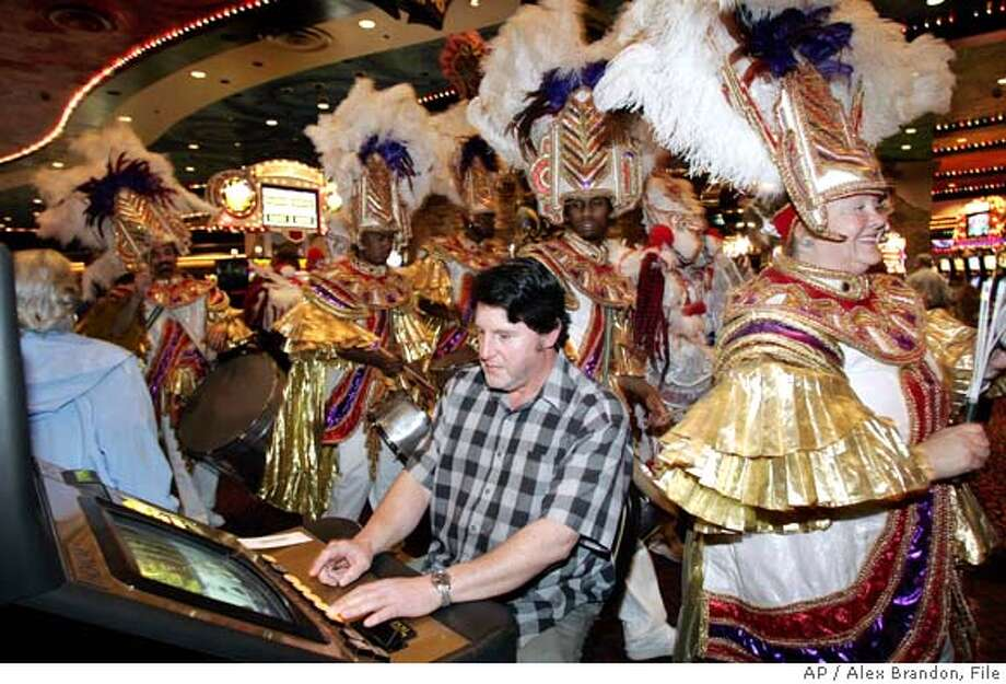 Donald Waguespack from St. Rose, LA plays the slots as Casa Samba play and dance through Harrah's Casino on their first day open after Hurricane Katrina in New Orleans on Friday Feb. 17, 2006. (AP Photo/Alex Brandon) Photo: ALEX BRANDON