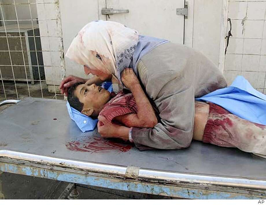 ** EDS NOTE GRAPHIC CONTENT ** A woman takes her dead son into her arms, as she grieves for her six-year-old son, Dhiya Thamer, who was killed when their family car came under fire by unknown gunmen in Baqouba, capital of Iraq's Diyala province, 60 kilometers (35 miles) northeast of Baghdad, Iraq, on Sunday, Sept. 16, 2007. The boy's ten-year old brother, Qusay, was injured in the attack as the family returned from enrolling the children in school, where Dhiya was to begin his first year. (AP Photo) EDS NOTE GRAPHIC CONTENT Photo: Ap