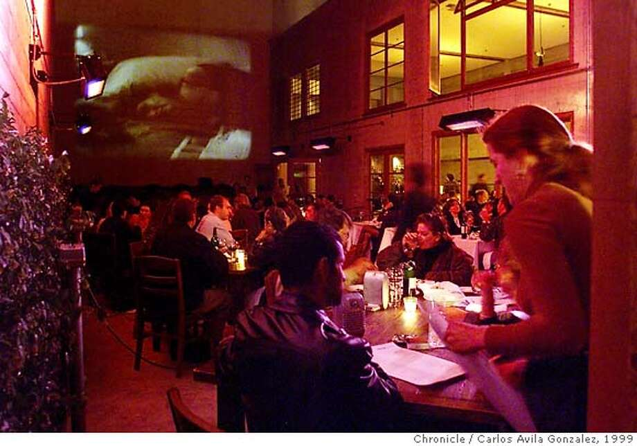 """WHATS.25 A/C/19AUG99/FD/CG --- The outdoor dining area at foreign Cinema Restaurant features and open air theater, which was showing, """"La Dolce Vita,"""" on Thursday night, August 19, 1999. (CARLOS AVILA GONZALEZ/SAN FRANCISCO CHRONICLE) CAT Photo: CARLOS AVILA GONZALEZ"""