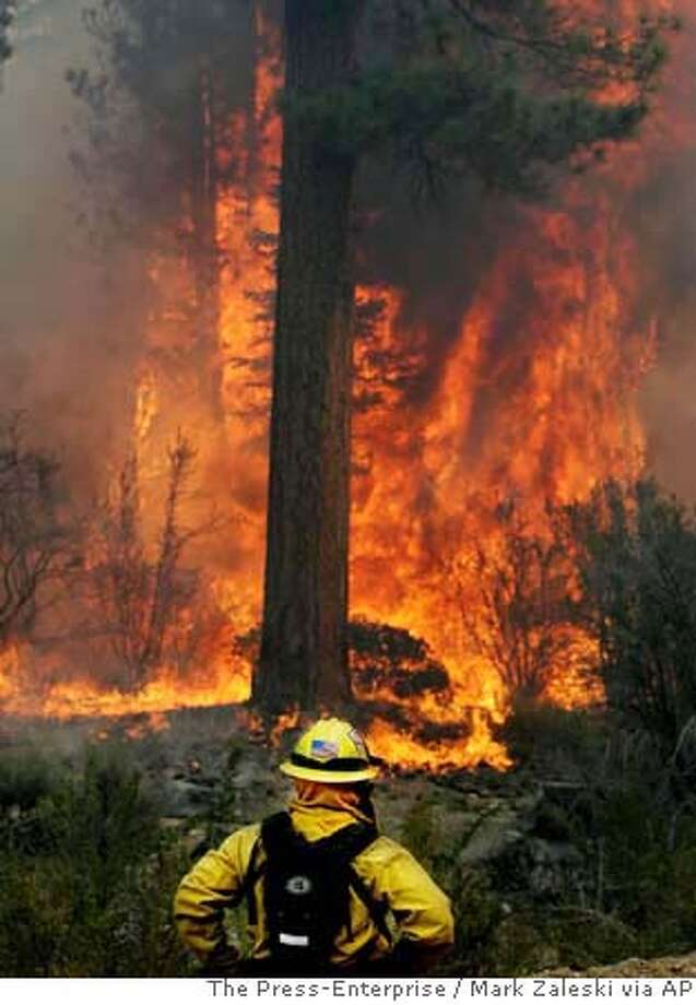 A firefighter watches as several pine trees go up in flames after backfires were set in front of the oncoming Butler II Fire near Holcomb Valley, Calif., Sunday, Sept. 16, 2007. Firefighters Sunday were battling two raging wildfires in Southern California that forced nearly 2,000 people to evacuate. (AP Photo/The Press-Enterprise, Mark Zaleski) ** MANDATORY CREDIT, NO SALES, MAGS OUT ** ( NO SALES, MAGS OUT, MANDATORY CREDIT Photo: Mark Zaleski