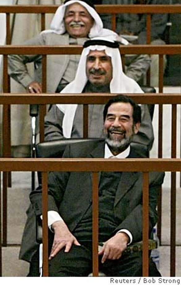 Former Iraqi President Saddam Hussein and co-defendants laugh at his trial in Baghdad Photo: BOB STRONG