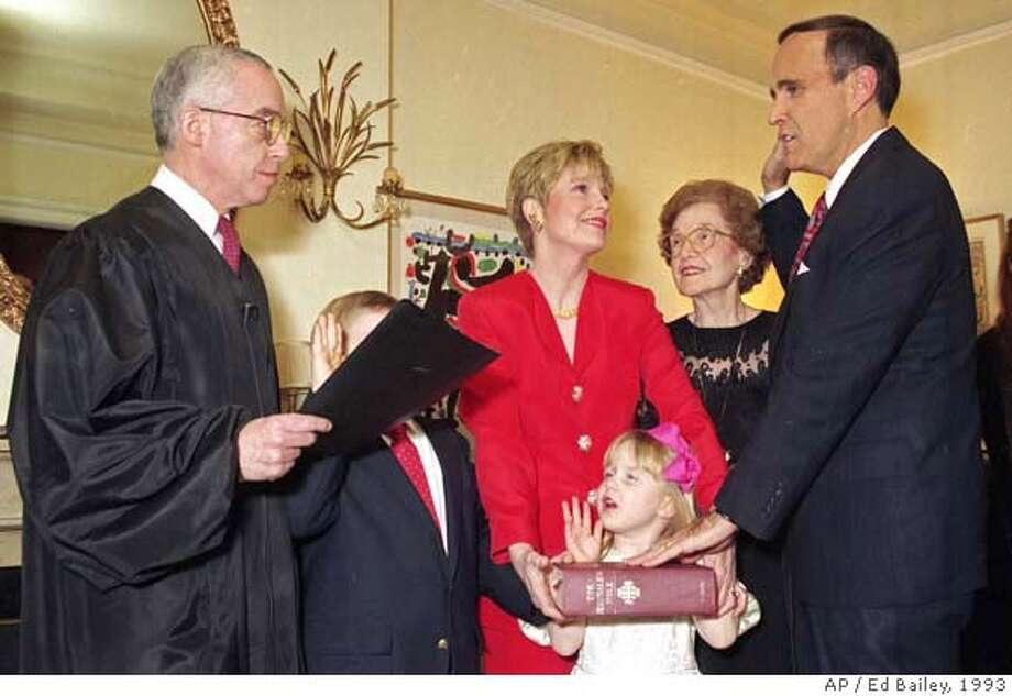 ** FILE ** Rudy Giuliani, right, is symbolically sworn-in as New York City Mayor by U.S. District Court Judge Michael B. Mukasey, left, during a private ceremony in New York in this Dec. 31, 1993 file photo. Giuliani's wife Donna Hanover, center, stands with their children Andrew, 7, and Caroline, 4; Giuliani's mother Helen looks on. Conservatives on Saturday lined up for and against potential attorney general nominee Michael Mukasey who they believe has ascended to the top of President Bush's list of replacements for Alberto Gonzales. (AP Photo/Ed Bailey, File)  Ran on: 09-16-2007  Michael Mukasey, shown in 1993, was nominated to the federal bench by Reagan. A DEC. 31, 1993 FILE PHOTO Photo: ED BAILEY