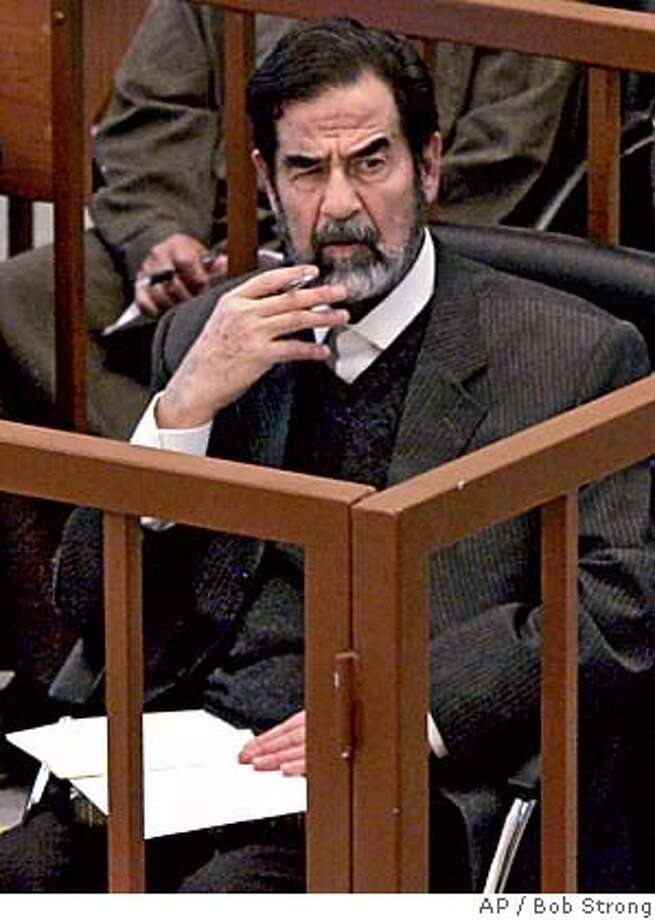 Former Iraqi President Saddam Hussein listens to one of the prosecutors as his trial resumes in Baghdad Tuesday, Feb. 28, 2006. Saddam and seven co-defendants are on trial for torture, illegal arrests and the killing of nearly 150 people from Dujail after a 1982 assassination attempt on Saddam in the town. They face death by hanging if convicted. (AP Photo/Bob Strong, Pool) POOL PHOTO Photo: BOB STRONG