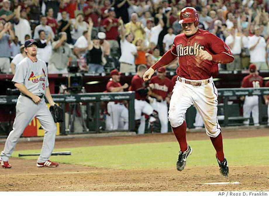 St. Louis Cardinals pitcher Ryan Franklin, left, watches Arizona Diamondbacks' Eric Byrnes score the winning run in the seventh inning of a baseball game Sunday, Sept. 9, 2007, in Phoenix. Franklin was the loser for the Cardinals, giving up four runs in the seventh inning of the 6-5 loss. (AP Photo/Ross D. Franklin) Photo: Ross D. Franklin